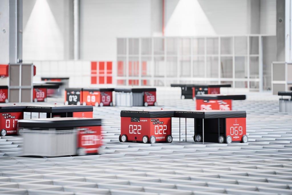 Varios robots de línea roja de AutoStore moviéndose rápidamente en una cuadrícula
