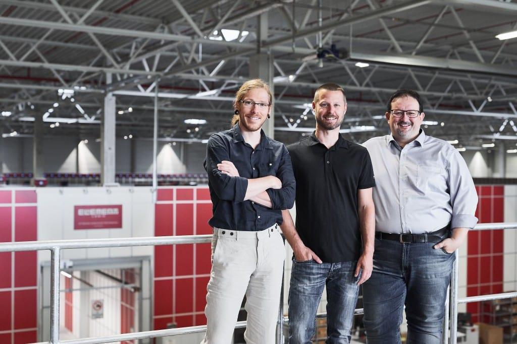 Thomas Klein y Ronny Höhn, de Bergfreunde, y Michael Kawalier, de Element Logic, delante de la parrilla de AutoStore