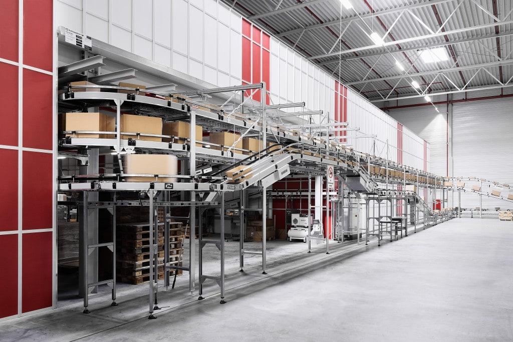Cinta transportadora con cajas en movimiento entrando y saliendo de las instalaciones de AutoStore
