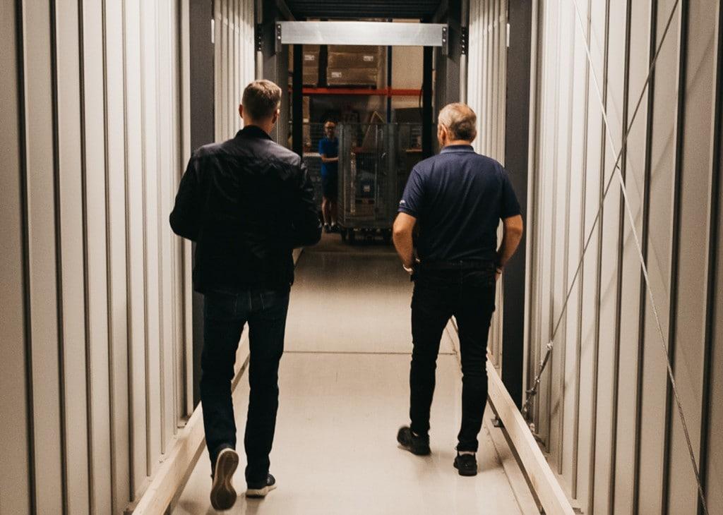 El cofundador de GS Bildeler, Trond Gule, y el director de ventas de Element Logic, Øyvind Kollerud, recorren el túnel hecho a medida a través del sistema AutoStore en el almacén de Oslo.