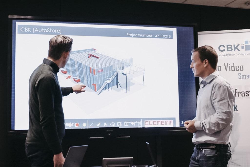 Dos hombres señalan y miran la presentación de un dibujo de una solución AutoStore.
