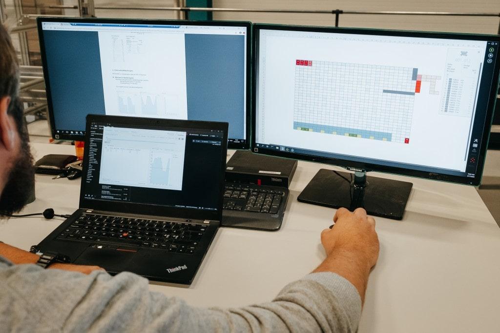 Un hombre trabaja en la solución AutoStore con tres pantallas de ordenador.