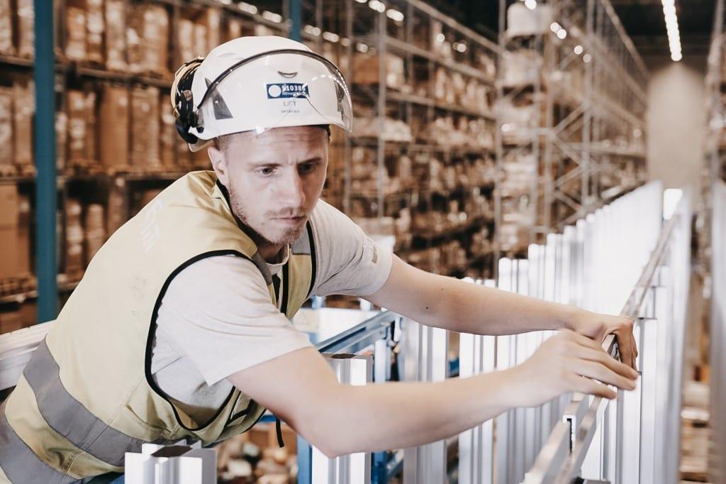 Un hombre con casco y chaleco amarillo está construyendo la cuadrícula del AutoStore.