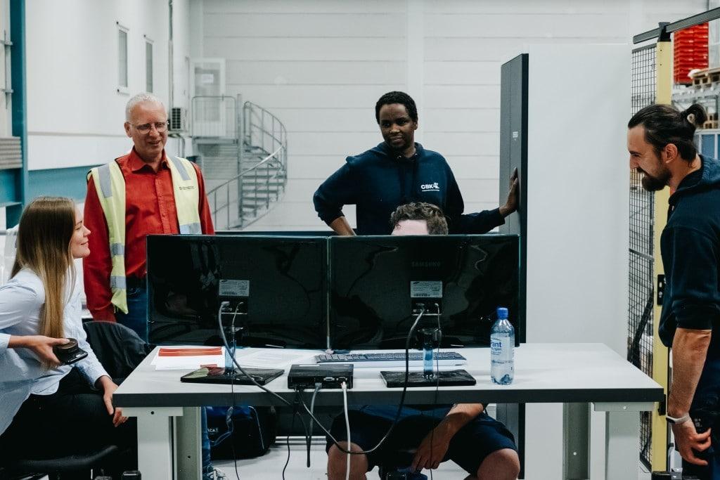 Cinco personas trabajan juntas frente a un sistema informático para aprender a manejar el sistema AutoStore.