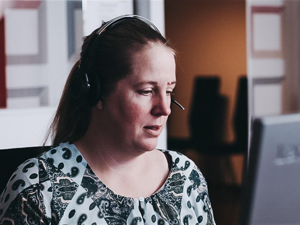 Un primer plano de una mujer hablando con auriculares delante de un ordenador.
