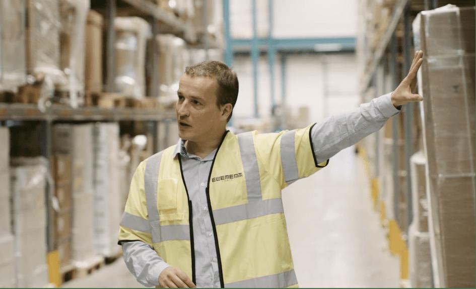 Un hombre en un chaleco amarillo en un almacén está señalando y mirando algo fuera de la toma de la cámara.