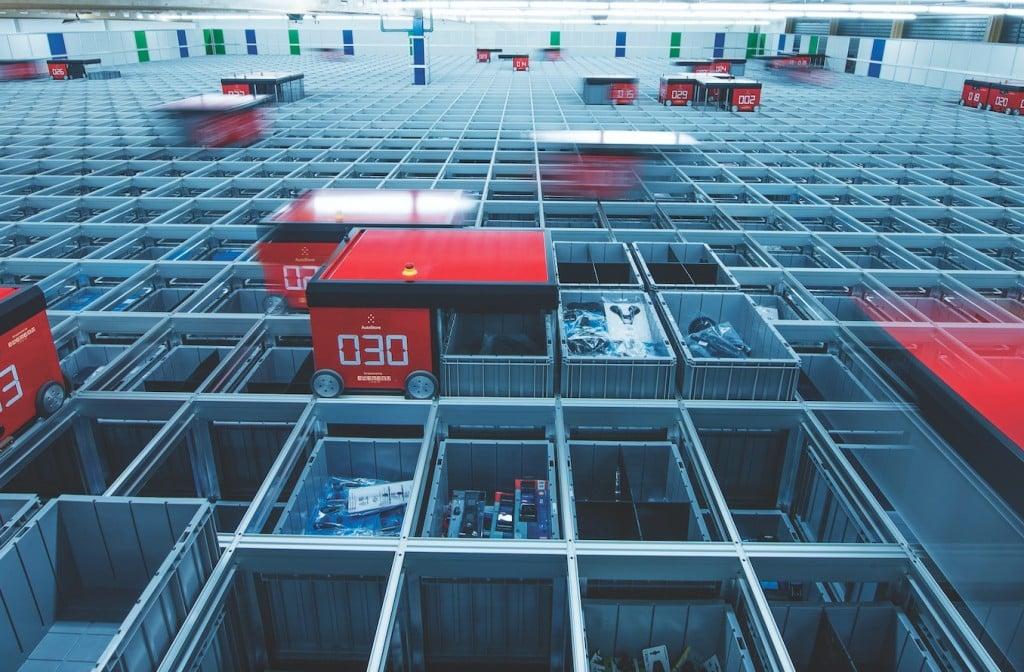 Imagen de las cubetas llenas con artículos y de los robots de AutoStore en pleno funcionamiento