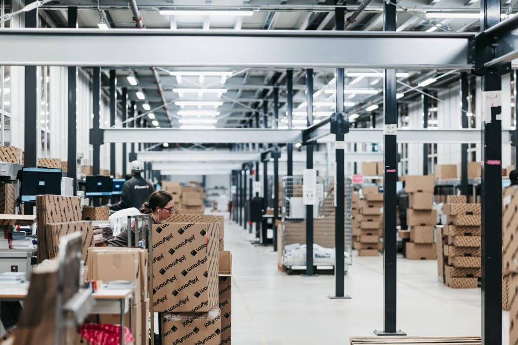 Imagen de un pasillo de un almacén logístico lleno de cajas de cartón