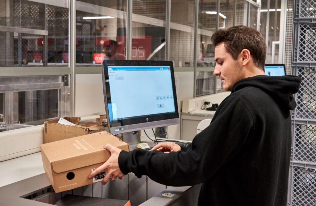 Operario de almacén preparando un pedido en una estación de trabajo